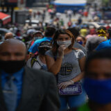 People wear face masks as they walk along Sabana Grande Boulevard after the government eased a nationwide lockdown as a preventive measure against the COVID-19 coronavirus, in Caracas, on June 3, 2020. - Banks, shoe stores and hairdressers reopened this week in Venezuela in a relaxation of the quarantine in force since mid-March due to the COVID-19 pandemic, coinciding with kilometer-long lines of vehicles waiting for turns at gasoline pumps. (Photo by Federico PARRA / AFP)
